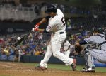 Minnesota Twins' Eduardo Escobar hits a two-run single off Cleveland Indians pitcher Corey Kluber in the fourth inning of a baseball game, Wednesday, Sept. 23, 2015, in Minneapolis. (AP Photo/Jim Mone)