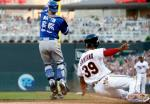 Minnesota Twins' Danny Santana, right, scores on a Joe Mauer single as Toronto Blue Jays catcher Russell Martin jumps for the throw during the third inning of a baseball game Thursday, May 19, 2016, in Minneapolis. (AP Photo/Jim Mone)