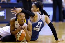 Indiana Fever's Tamika Catchings, left, tries to call a time out as she scrambles on the floor with Minnesota Lynx's Maya Moore in the second half of Game 4 of the WNBA Finals basketball series, in Indianapolis, Sunday, Oct. 11, 2015.  (AP Photo/Michael Conroy)