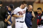Minnesota Twins pitcher Phil Hughes is helped off the field by trainer Tony Leo, right, and manager Paul Molitor, left, after he was hit in the knee with a line drive by Miami Marlins' J.T. Realmuto during the ninth inning of a baseball game Thursday, June 9, 2016, in Minneapolis. The Marlins won 10-3. (AP Photo/Jim Mone)