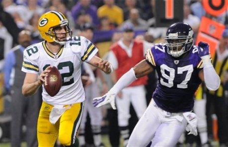 El quarterback Aaron Rodgers (12), de los Packers de Green Bay, trata de evadir al defensive end Everson Griffen, derecha, de los Vikings de Minnesota, durante la segunda mitad del partido del domingo 23 de octubre de 2011, en Minneápolis, Minnesota. (Foto AP/Jim Mone)