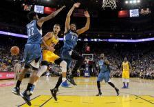 Golden State Warriors' Stephen Curry (30) makes a behind-the-back pass under the basket as Minnesota Timberwolves' Andrew Wiggins (22) and Karl-Anthony Towns (32) defend during the first half of an NBA basketball game Tuesday, April 5, 2016, in Oakland, Calif. (AP Photo/Marcio Jose Sanchez)
