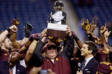 Minnesota head coach Tracy Claeys holds the winner's trophy after the Quick Lane Bowl NCAA college football game against Central Michigan, Monday, Dec. 28, 2015, in Detroit. Minnesota defeated Central Michigan 21-14. (AP Photo/Carlos Osorio)