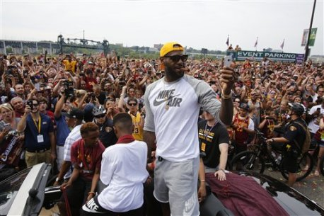 Cleveland Cavaliers' LeBron James, center, takes a selfie as he stands in the back of a Rolls Royce as it makes it way through the crowd lining the parade route in downtown Cleveland, Wedensday, June 22, 2016, celebrating the Cleveland Cavaliers' NBA Championship. (AP Photo/Gene J. Puskar)