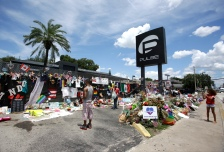 This photo taken July 11, 2016, shows visitors taking photos and leaving items at a makeshift memorial outside the Pulse nightclub, the day before the one month anniversary of a mass shooting, in Orlando, Fla. (AP Photo/John Raoux)
