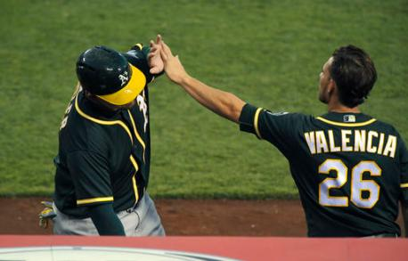 Oakland Athletics' Billy Butler, left, is congratulated by Danny Valencia after scoring on a single by Marcus Semien during the 10th inning of a baseball game against the Los Angeles Angels, Thursday, Aug. 4, 2016, in Anaheim, Calif. The Athletics won 8-6  in 10 innings. (AP Photo/Mark J. Terrill)