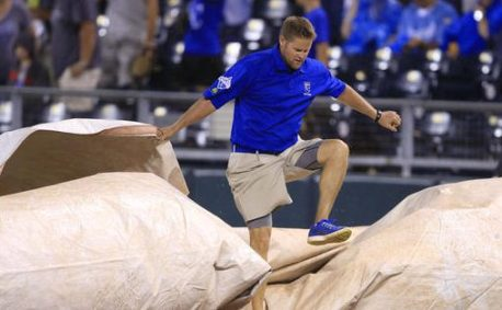 A grounds crew member works to cover the field during the fifth inning of a baseball game between the Kansas City Royals and the Minnesota Twins at Kauffman Stadium in Kansas City, Mo., Friday, Aug. 19, 2016. (AP Photo/Orlin Wagner)