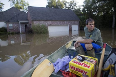 David Key boats away from his flooded home after reviewing the damage in Prairieville, La., Tuesday, Aug. 16, 2016. Key, an insurance adjuster, fled his home as the flood water was rising with his wife and three children and returned today to assess the damage. (AP Photo/Max Becherer)