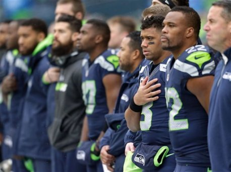 Seattle Seahawks running back Fred Jackson (22), quarterback Russell Wilson (3) and others line up for the National Anthem before an NFL football game against the St. Louis Rams, Sunday, Dec. 27, 2015, in Seattle. (AP Photo/John Froschauer)