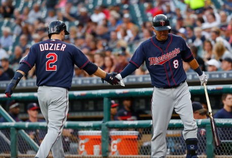 Minnesota Twins' Brian Dozier (2) celebrates scoring with Kurt Suzuki (8) on a Robbie Grossman two-run single during the first inning of a baseball game in Detroit, Tuesday, Sept. 13, 2016. (AP Photo/Paul Sancya)