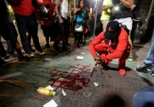 A man squats near a pool of blood after a man was injured during a protest of Tuesday's fatal police shooting of Keith Lamont Scott in Charlotte, N.C. on Wednesday, Sept. 21, 2016. Protesters rushed police in riot gear at a downtown Charlotte hotel and officers have fired tear gas to disperse the crowd. At least one person was injured in the confrontation, though it wasn't immediately clear how. Firefighters rushed in to pull the man to a waiting ambulance. (AP Photo/Chuck Burton)
