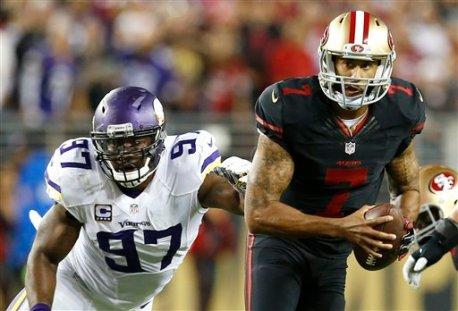 San Francisco 49ers quarterback Colin Kaepernick (7) scrambles away from Minnesota Vikings defensive end Everson Griffen (97) during the first half of an NFL football game in Santa Clara, Calif., Monday, Sept. 14, 2015. (AP Photo/Tony Avelar)