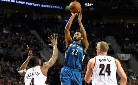 Minnesota Timberwolves guard Andrew Wiggins (22) shoots the ball over Portland Trail Blazers forward Maurice Harkless (4) and center Mason Plumlee (24) during the first quarter of an NBA basketball game in Portland, Ore., Saturday, April 9, 2016. (AP Photo/Steve Dykes)