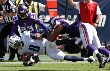 Tennessee Titans quarterback Marcus Mariota (8) is brought down by Minnesota Vikings defenders Eric Kendricks (54) and Terence Newman (23) in the first half of an NFL football game Sunday, Sept. 11, 2016, in Nashville, Tenn. (AP Photo/James Kenney)
