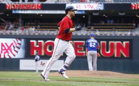 Minnesota Twins' Brian Dozier jogs home on his eighth-inning solo home run off Kansas City Royals pitcher Brooks Pounders, right, in a baseball game Monday, Sept. 5, 2016, in Minneapolis. It was Dozier's third home run of the game. The Royals won 11-5. (AP Photo/Jim Mone)
